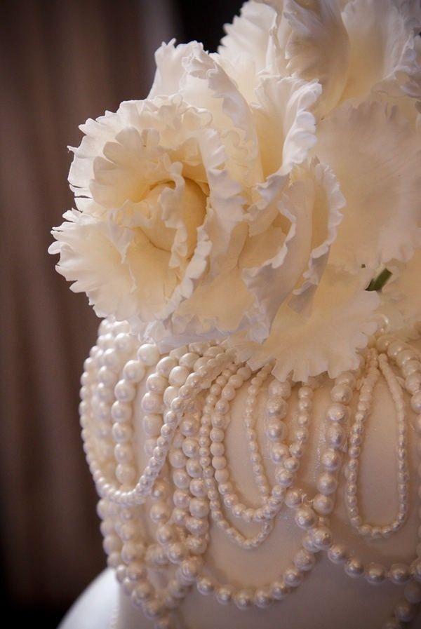 Pastel de bodas con perlas de fondant y una enorme flor coronando en la altura | 25 Imágenes de Pasteles de Boda Originales e Irresistibles