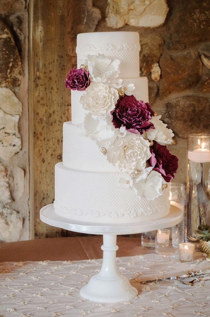 Delicadosdetalles de color. Este pastel de boda blanco con detalles en suave relieve luce una cascada de flores comestibles blancas y marsala con bolitas doradas.