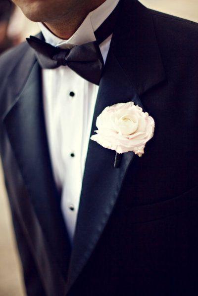 El clásico traje de novio en negro con una flor blanca en la solapa es el estilo ideal para una boda clásica y elegante. Acompañado de un corbatín negro tendremos el estilo más formal para novios.