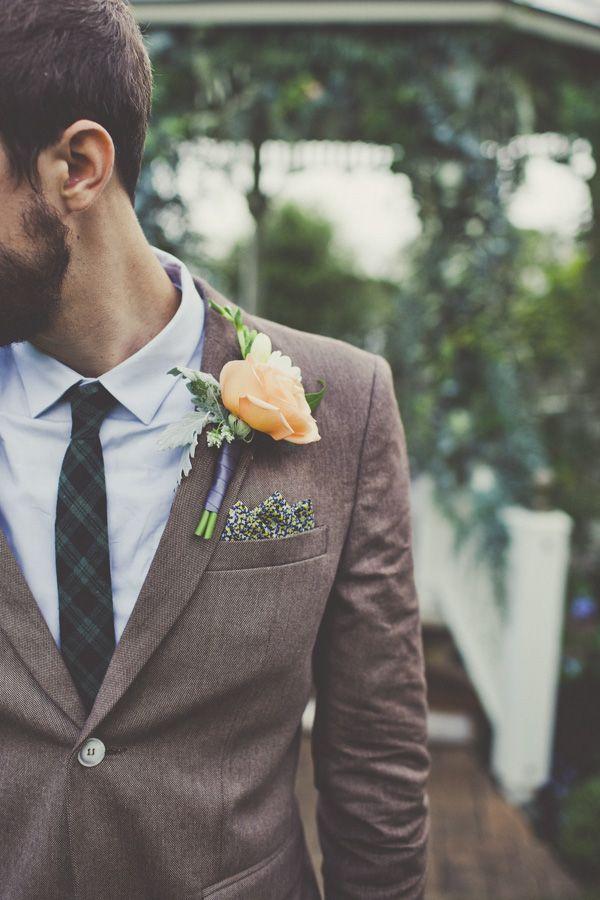 La flor en la solapa del traje de novio le diferencia de los invitados. Traje moderno con boutoniere en color durazno para boda estilo campestre chic o boho chic. Fotografía de weddingchicks.com.