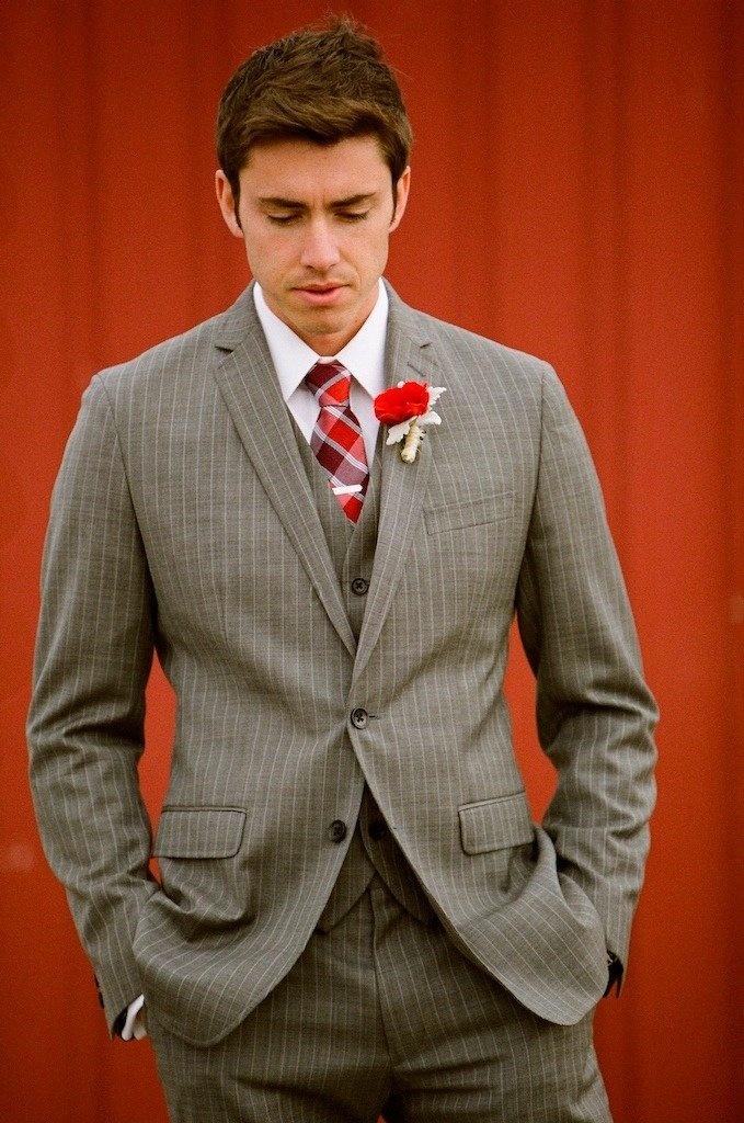 Un traje de novio en color claro con rayas gruesas es una buena idea para novios modernos y divertidos. Combinacion perfecta para una boda que combine los rojos de la corbata y el boutoniere. Fotografia baplove.com