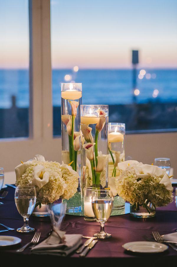 Una vista de lujo para una boda de envidia con centros de mesa sencillos - agua flores velas y floreros