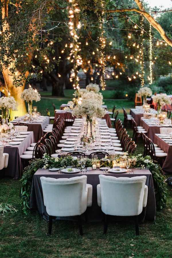 Más luces navideñas para esta decoración de bodas hecha por The Knot, ¡nada más ni nada menos! Los centros de mesa muy bellos y económicos con baby's breath le dan un look muy moderno a esta boda al aire libre.