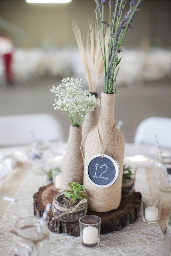 Para hacer estos números para mesas de boda envuelve una botella de vino con hilo sisal, agrega unas flores y el número de mesa en una etiqueta. Es fácil de hacer y luce perfecta en bodas rústicas o náuticas
