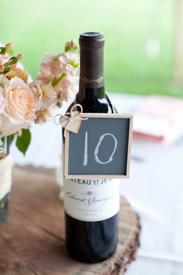 Pizarra con el número de mesa sobre una botella de vino - Fotografia: D Photography