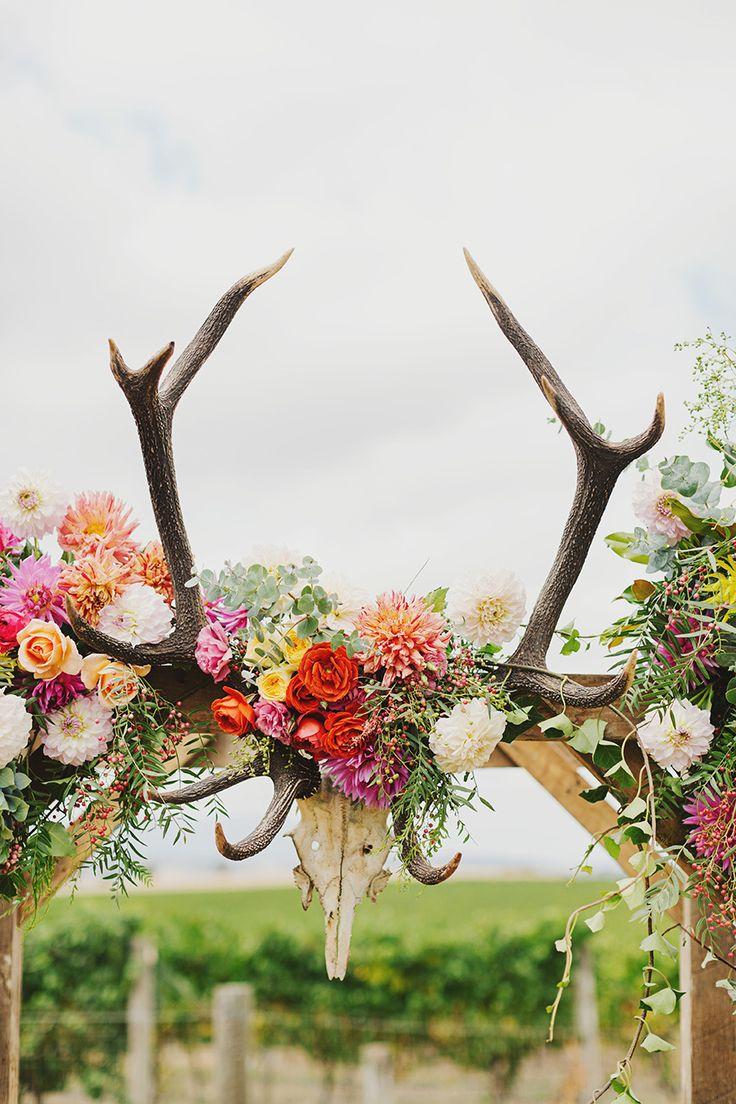Una enramada con el craneo de un toro con flores silvestres y coloridas - Fotografia Jonathan Ong