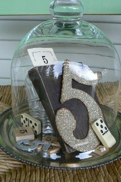 Centro de mesa y números para mesas de boda todo en uno. El número se repite de varias maneras.
