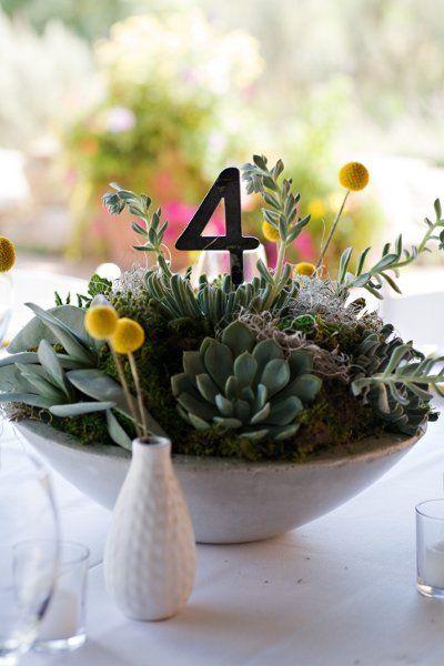 Alucinante centro de mesa con suculentas y número de mesa, rodeado de Craspedia amarilla diseñada por Realiza Planning.