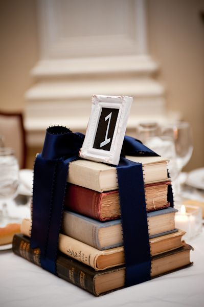 Originales números de mesa para bodas. En lugar de flores apila libros, átalos con un lazo, y agrega un marco con el número de mesa arriba ¡Voilá!