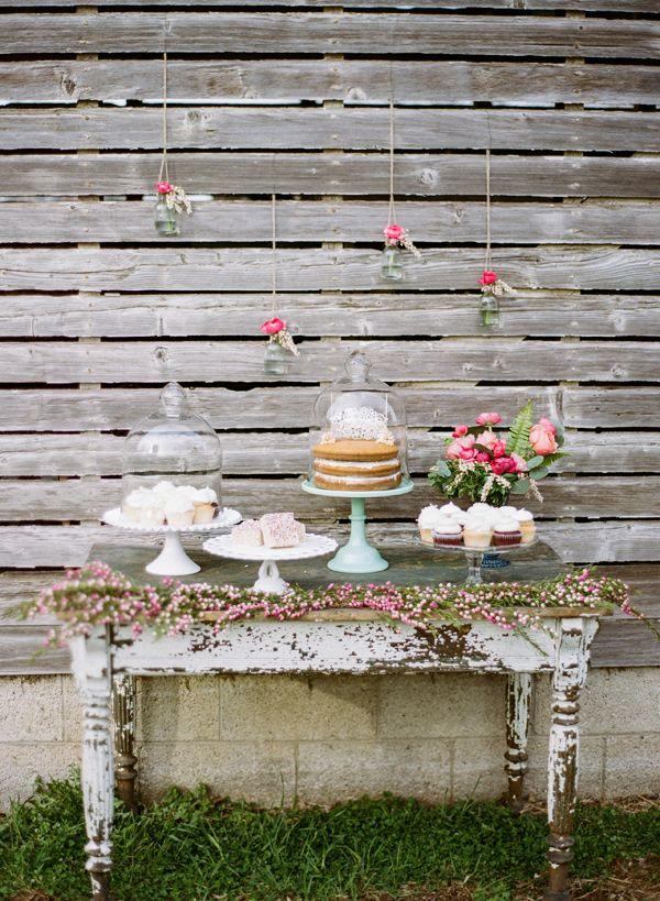 Adorable mesa para el pastel de bodas con flores colgantes. Foto Lauren Fair Photography
