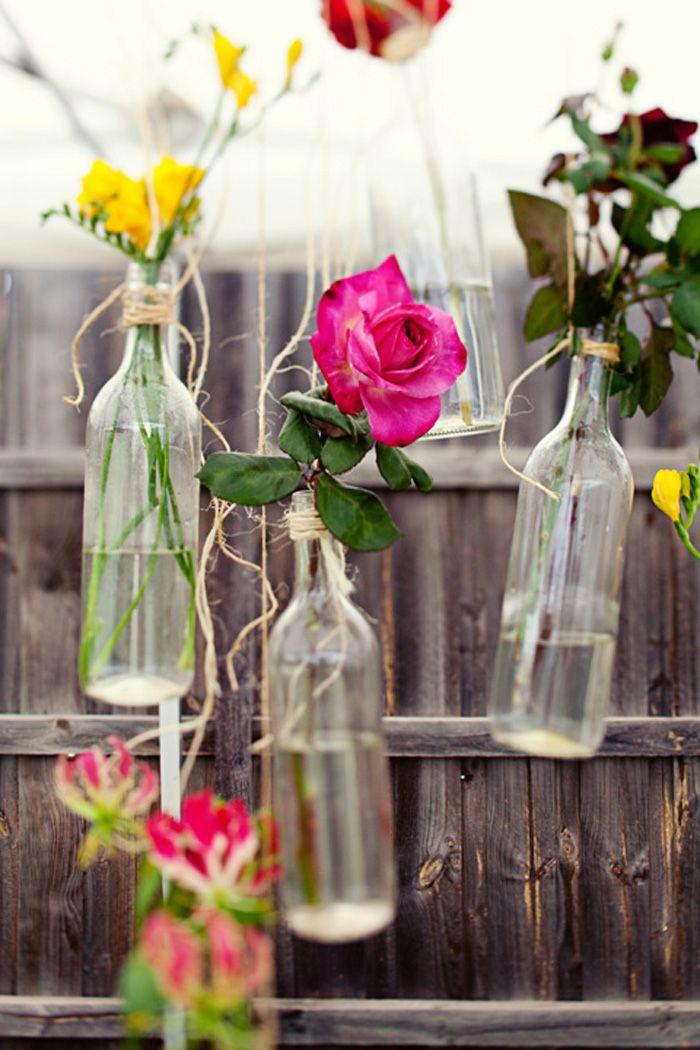 Originales mensajes en botellas. Decoración con botellas y flores colgantes.