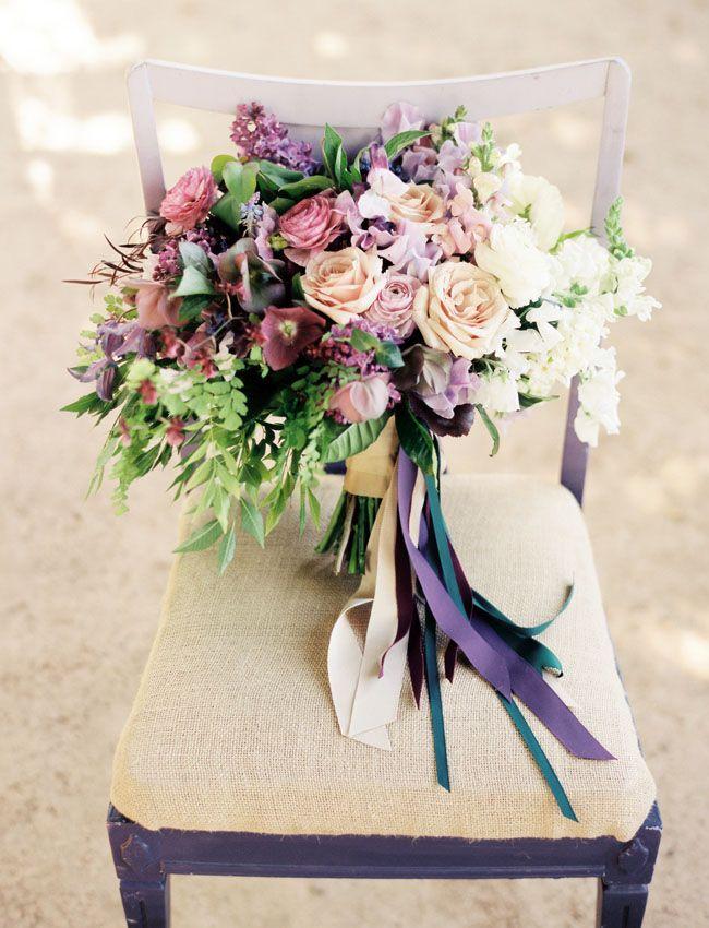 Ramo de novia lleno de detalles intricados, flores gigantes y sutiles y flores conejito en tonos lilas y morados. Fotografía: Ryan Johnson Photography