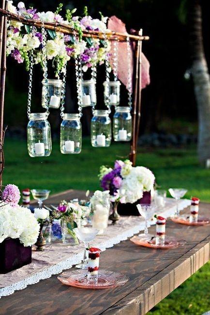 Velas en frascos colgando sobre las mesas para esta boda boho.