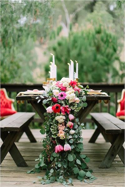 Guirnaldas de flores en el caminito de una mesa larga y vintage