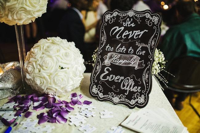 Un cartel pizarra da la bienvenida a esta boda para una pareja divertida. Mesa del libro de firmas de invitados. Crédito de Fotografía Christian Turner