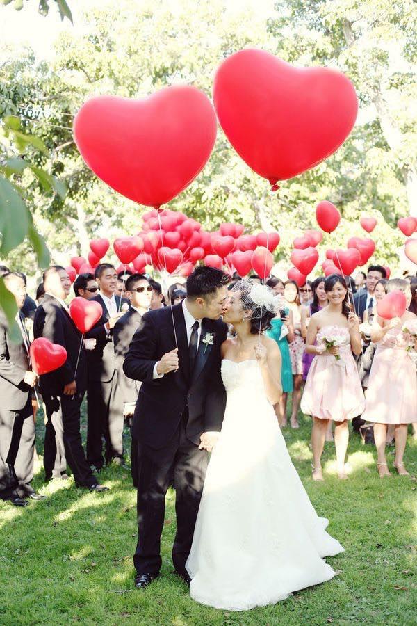 Una foto romántica. Original suelta de globos rojos en forma de corazón. Foto: Youkeun Oh Photography via Style Me Pretty