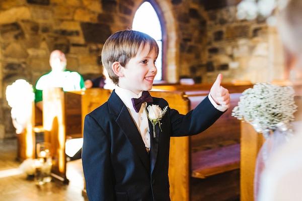 Una sonrisa gigante, moño y boutoniere. Traje para el paje de la boda. Crédito de Fotografía Christian Turner