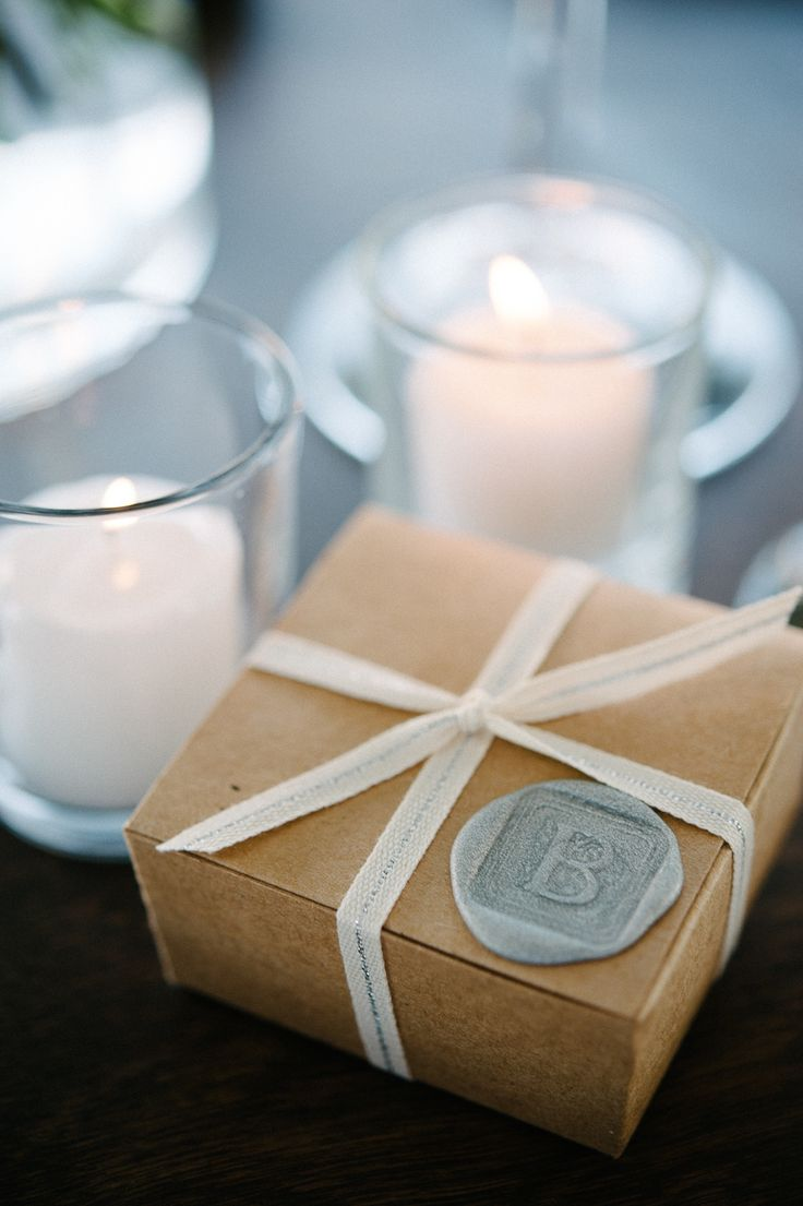 Da un toque único a tus souvenirs con sellos personalizados para bodas sobre cajas de carton con un lazo y una estampilla monogramada en cera.