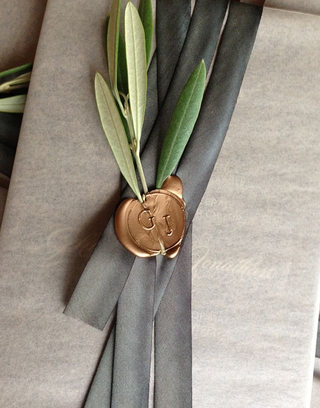 Sello de lacre de cera con una ramita de olivo en esta invitación diseñada por Sarah Drake