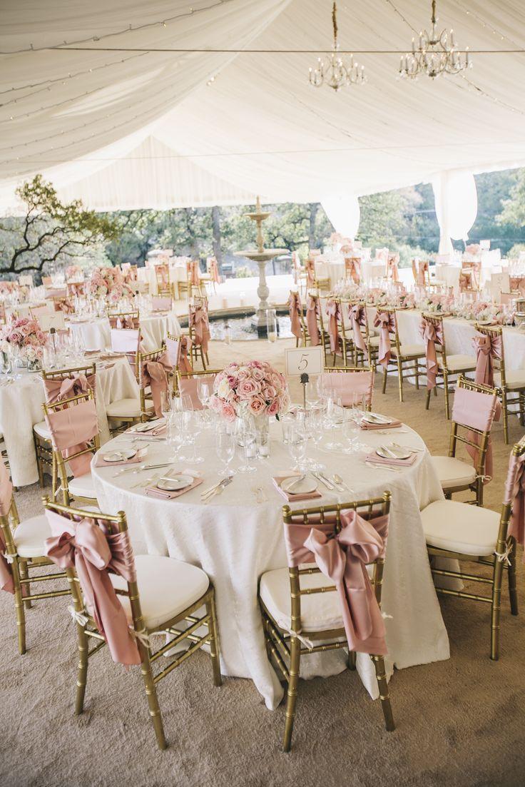 Una recepción en blanco y rosa con una carpa de tela y lámparas de araña colgantes.