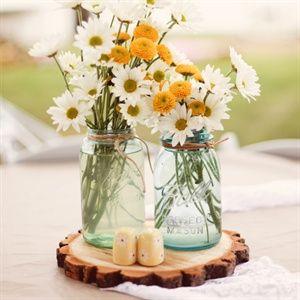 Centros de mesa country chic con mason jars, flores frescas, y base de madera.