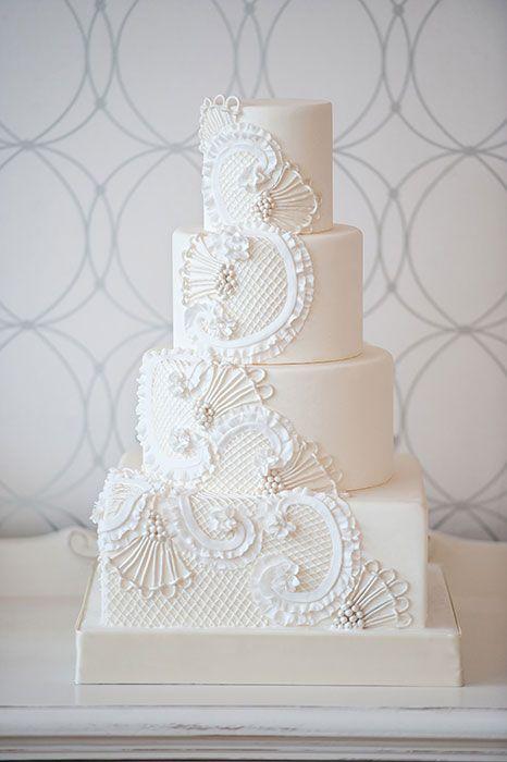 Elegante y chic torta de casamiento de cuatro pisos en blanco inspirada en el encaje del vestido de la novia por Bobbette & Belle.