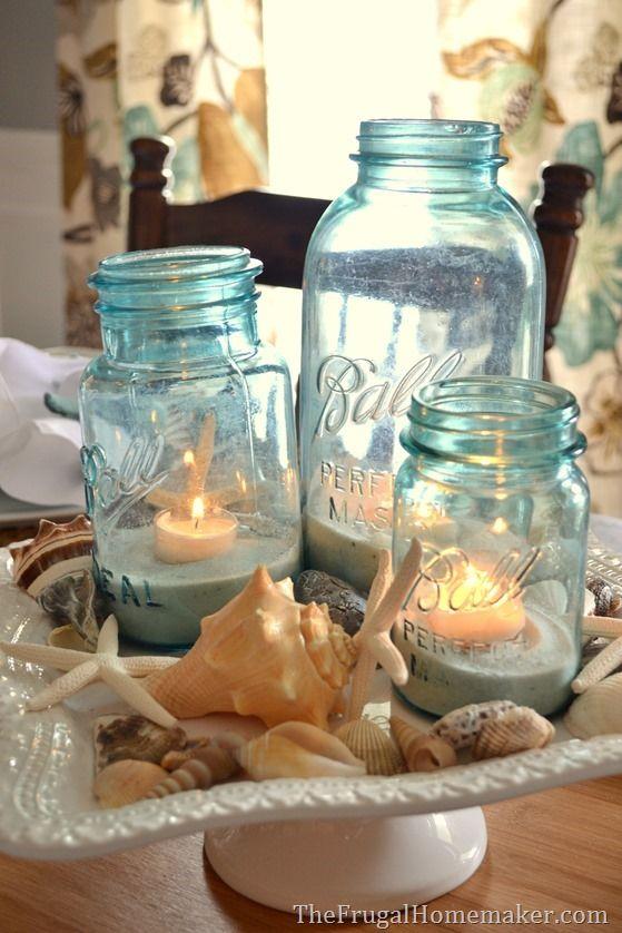 Ideas para usar Mason Jars para bodas en la playa. Arena y velas rodeadas de caracoles para un centro de mesa perfecto.