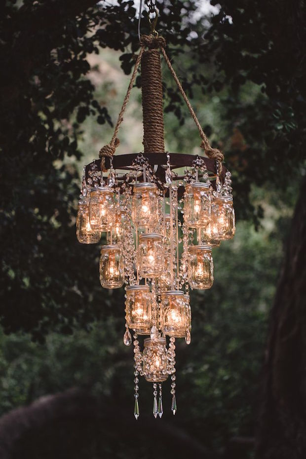 Ilumina tu boda con mason jars que cuelgan de la rueda de una carreta. Mas romántico imposible.