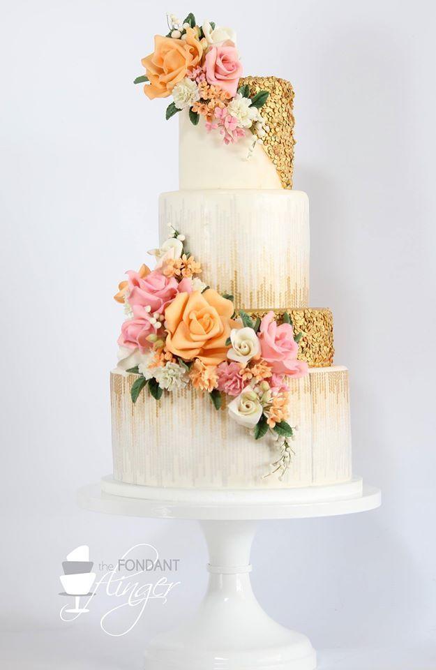 Pastel vintage en blanco y dorado confeccionado por Fondant Flinger de New Orleans. Adornado con dos cascadas de flores que completan el look retro