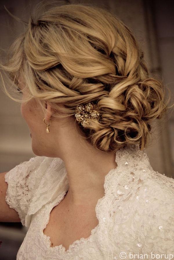 Peinado de novia con recogido bajo y un broche antiguo para boda vintage.