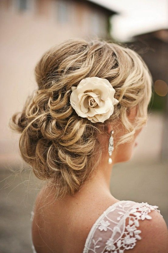 Peinado de novia con recogido bajo, una flor de seda y un par de bellos pendientes para lucir hermosa en tu boda