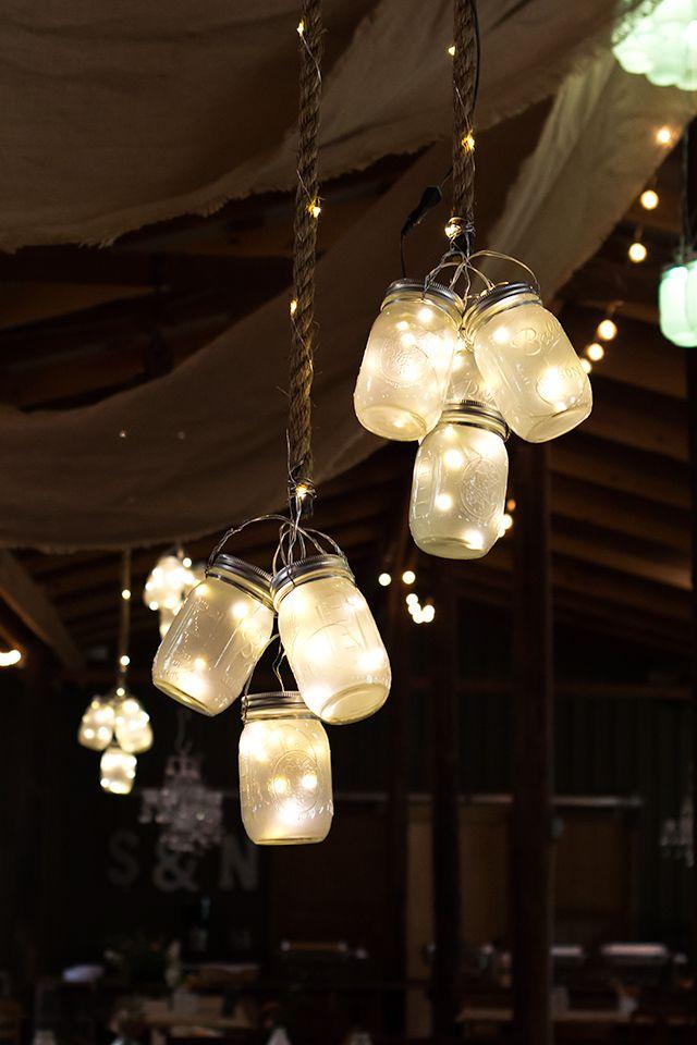 Racimos de luces LED en mason jars cuelgan del techo del granero en esta boda rústica. Magnífico y mágico.