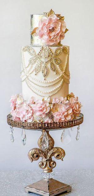 Torta vintage glam drapeada en perlas y rodeada de flores de seda sobre un soporte con caireles super retro.