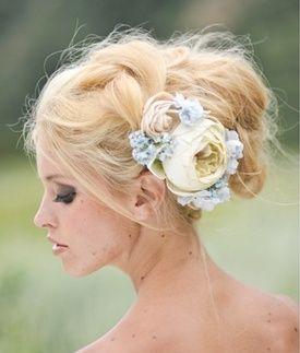 Un peinado recogido perfectamente desordenado, acentuado con un arreglo de flores en colores pastel que le da un toque boho y femenino.