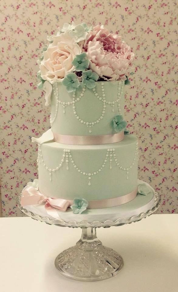 Cotton & Crumbs diseñó esta creación vintage en tonos pastel con detalles de joyas en fondant, flores y lazos.