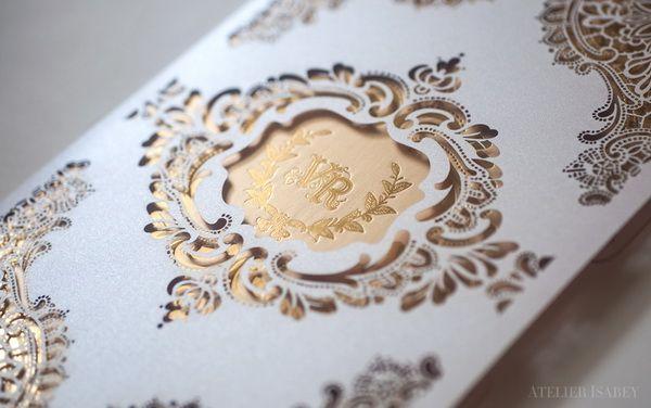 Un perfecto ejemplo que combina una invitación en dorado con estampado en letterpress dorado dentro de un sobre blanco con elaborado diseño en corte láser. Una creación de Atelier Isabey