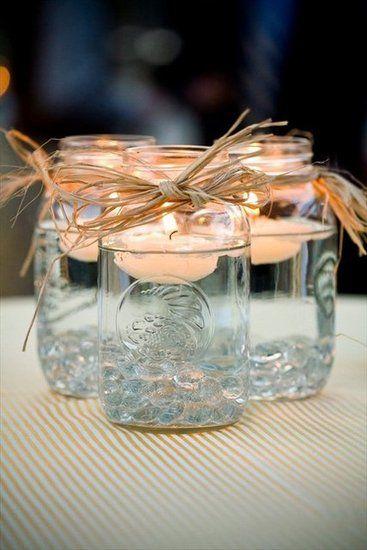 Iluminación para tu boda con mason jars y velas. Las piedritas de vidrio se compran por bolsa. Agrega agua y velas flotantes.