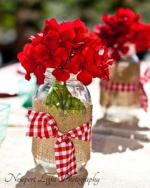 Arpillera y tela a cuadritos alrededor de los mason jars llenos de geranios. Perfecto para la decoración de tu boda.