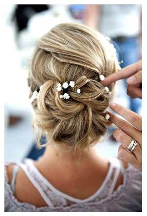 Unas flores adornan este precioso peinado recogido de novia