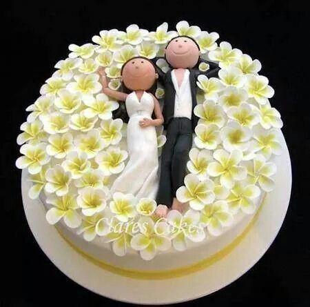 Una escena sobre la tarta nupcial con un par de adorable muñecos de torta.