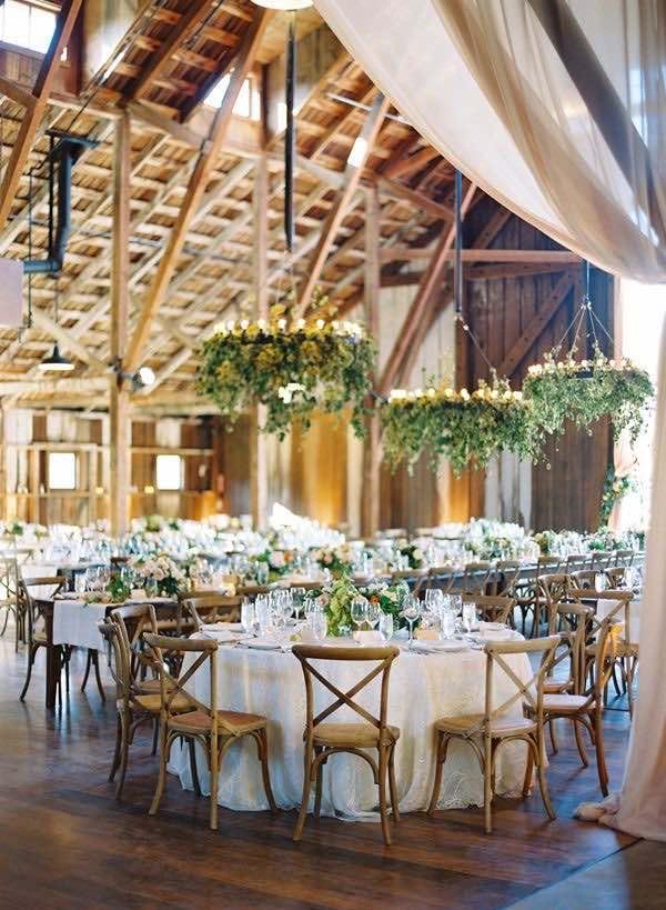 Arreglos florales para boda colgantes con luces y hiedra le dan un look mágico a la recepción de bodas. Fotografia: Jose Villa Photo