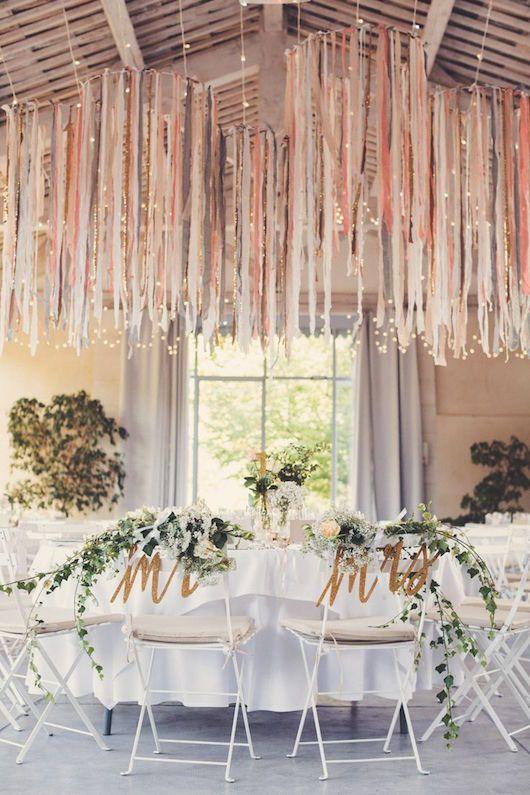 Centros de mesa colgantes con cintas en tonos complementarios a la boda. Outstanding!