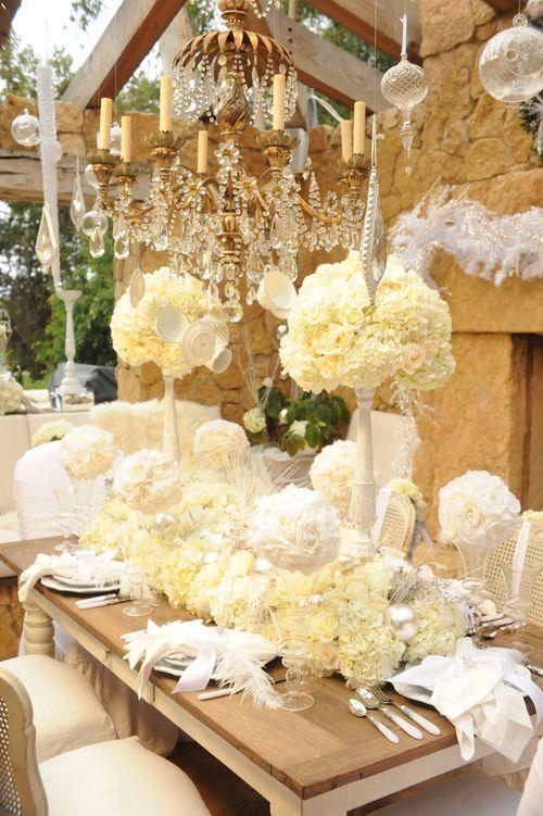 Chandeliers con caireles de cristal danzando sobre las mesas de esta boda de ensueño. Me fascina el detalle de las plumas sobre los platos de cada comensal.