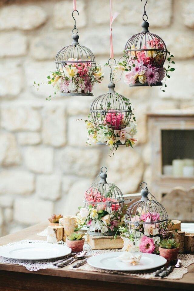 Jaulas con flores colgantes y más jaulas sobre la mesa de bodas un vintage boho total.