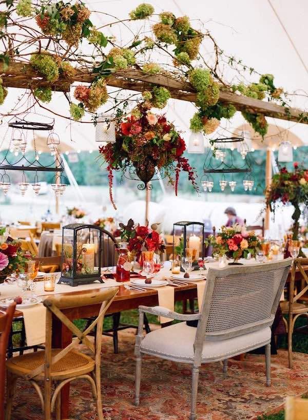 Los centros de mesa altísimos tocan el arreglo floral suspendido hecho con ramas y flores entrelazadas creado por Pat's Floral Designs y fotografiado por Jen Fariello Photograph