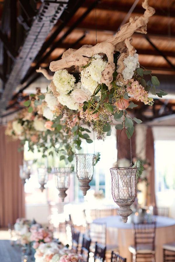 Ramas colgantes cubiertas en flores, ramas de laurel y linternas fotografiadas por Sarah Kate para una boda urbana inspirada en un jardín inglés.