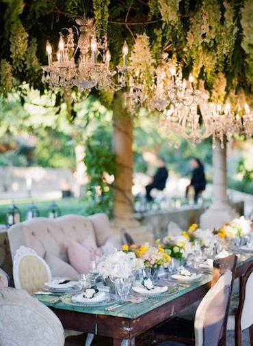 Una mezcla de chandeliers y follaje colgante en estos arreglos florales para bodas.