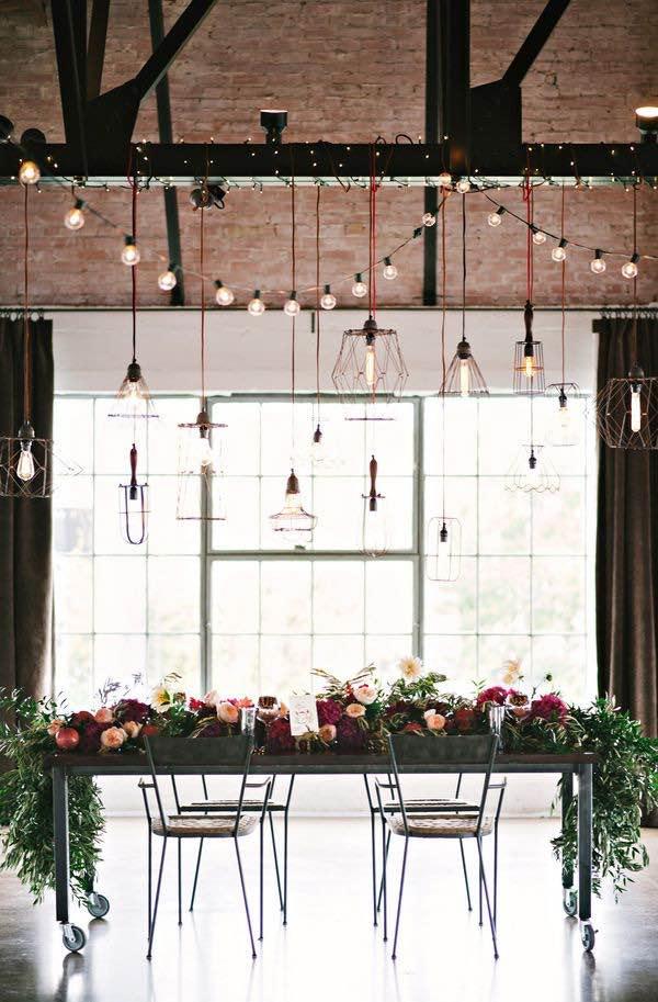 Me encanta esta mesa con rueditas que se puede sacar del medio una vez que empieza el baile. Centros de mesa colgantes con luces y lámparas de distintos estilos para una boda industrial.