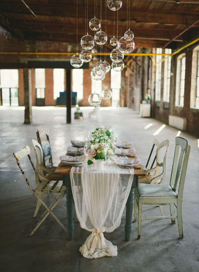 Nada mas apropiado que unos centros de mesa colgantes de vidrio en una fábrica de vidrio fotografiado por Kate Ignatowski Photography. Detalle y textura en una boda monocromática con unos pocos colores focales.
