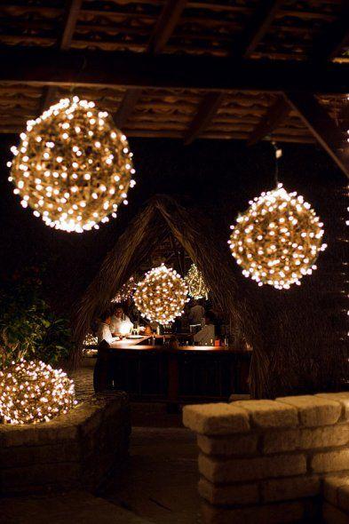 Si te gustan los chandeliers como centros de mesa colgantes pero tu presupuesto no te los permite, arma tus propias luces colgantes con algo redondo y cubierto de lucecitas de navidad.